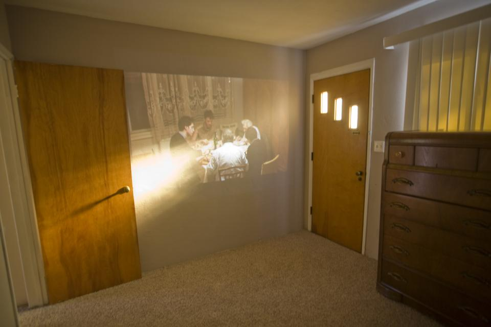 video projection of family dinner on wall in sunlit room
