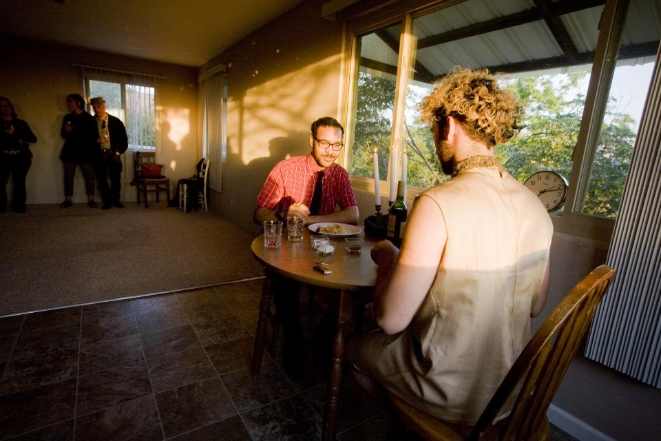 artist sitting with guest at dinner table in sunset light