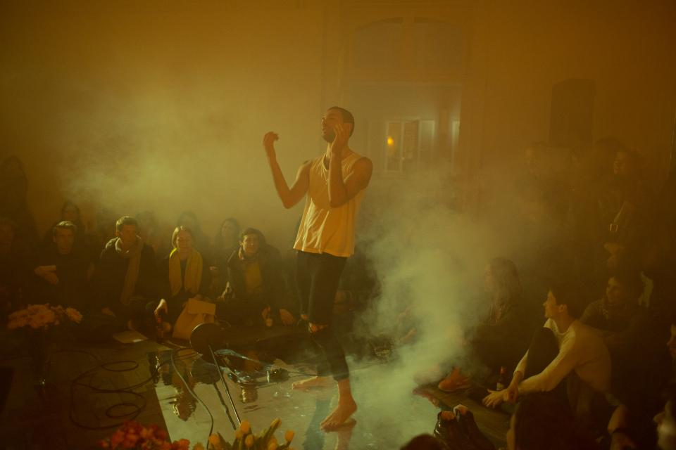 performer dancing in smoke, with audience