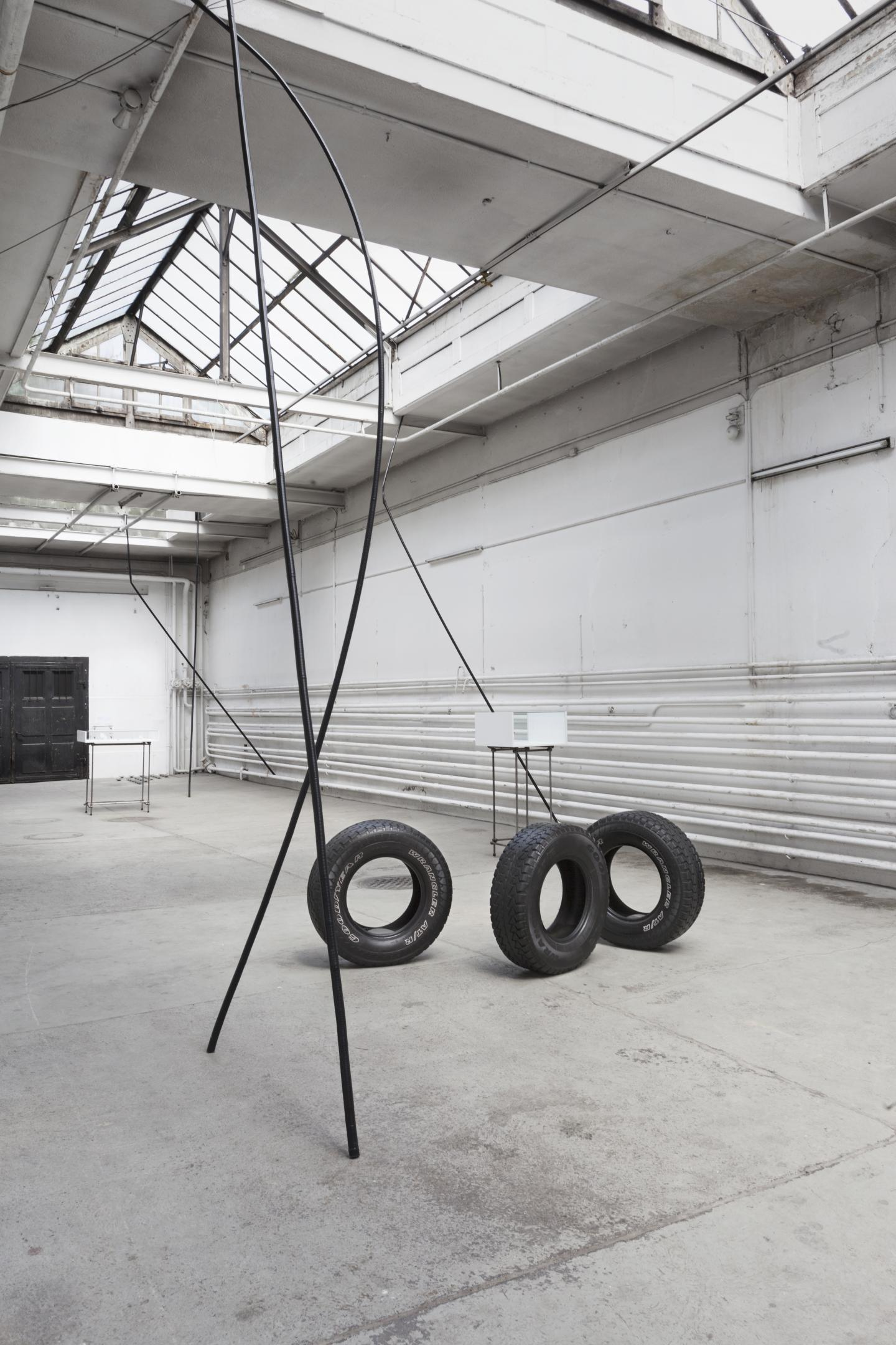 large black stick and tires installed in exhibition space
